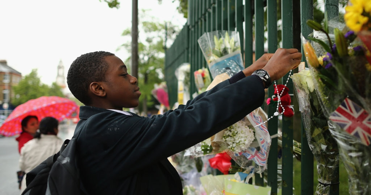 A young boy hangs a cross near flowers close to the scene where Drummer Lee Rigby of the 2nd Battalion the Royal Regiment of Fusiliers was killed, on May 24, 2013 in London, England. Drummer Lee Rigby of the 2nd Battalion the Royal Regiment of Fusiliers was murdered by suspected Islamists near London's Woolwich Army Barracks. The UK's security services are facing a Commons inquiry after confirmation that the two men arrested were known to MI5.</p>