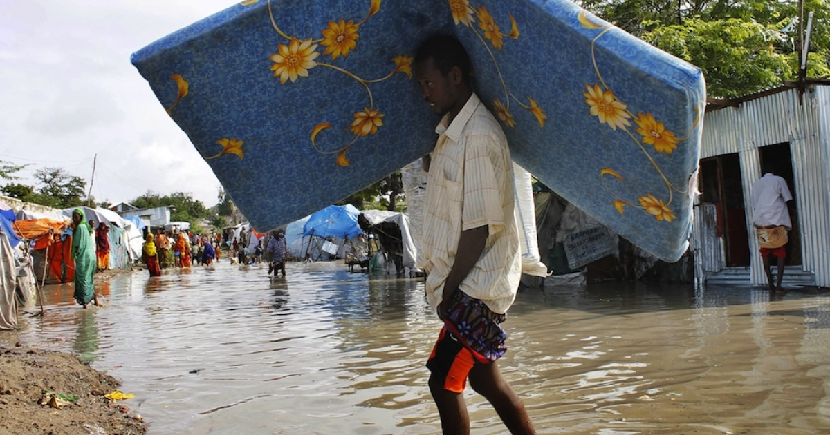 An internally displaced man carries some of his belongings through a flooded section of an IDP camp next to partially submerged cloth and twig shelters following heavy rain and flash floods in the Somalian capital, Mogadishu.</p>