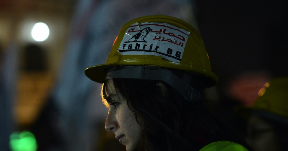 An Egyptian member of the Tahrir Bodyguards group wears a helmet which reads 'protecting Tahrir' during a demonstration against sexual harassment in Cairo on February 12, 2013.</p>
