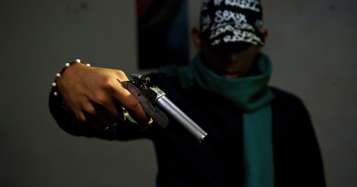 A gang member poses with a homemade gun at the Siloe neighborhood in Cali, Colombia on June 27, 2013. The United Nations has said that Latin America was the least secure region in the world due to crime.</p>