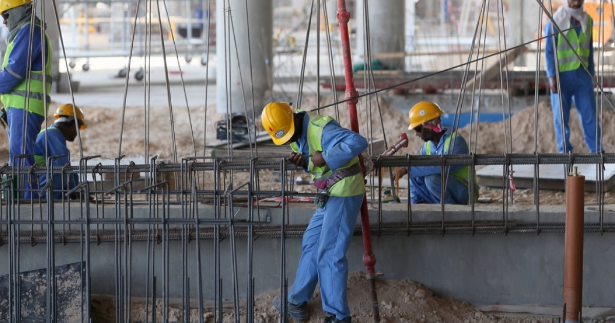 Migrant labourers work on a construction site on October 3, 2013 in Doha in Qatar. Qatar, the 2022 World Cup host, is under fire over claims of forced labour.</p>