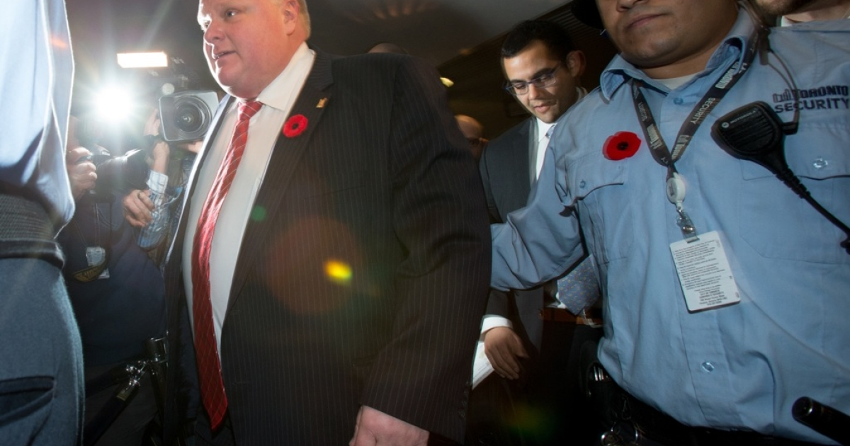 Mayor Rob Ford (C) leaves his office at Toronto City Hall on November 8, 2013 in Toronto, Ontario.</p>