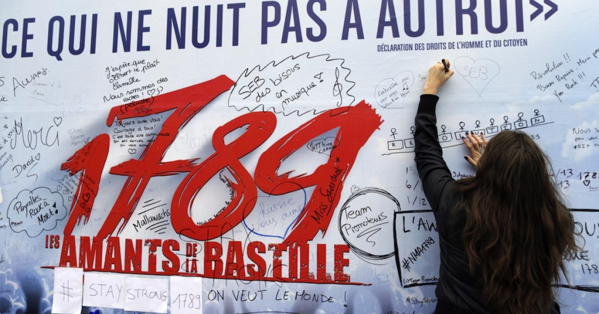 A woman writes down a message on the poster of the musical '1789, The Lovers of Bastille', on November 9, 2013 in Paris, one day after the blast at the Palace of Sports at the Porte de Versailles. One of around 15 people hurt in an accidental explosion during rehearsals for a Paris musical died overnight of a heart attack, police said today</p>