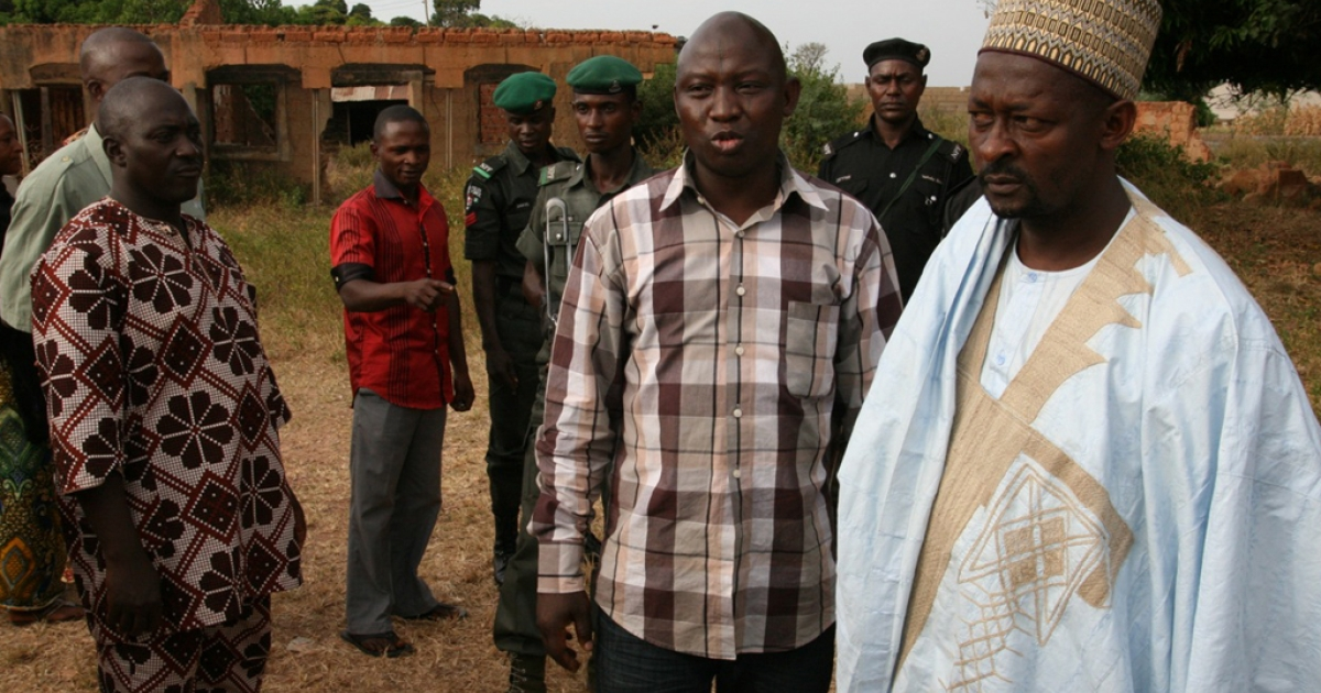 Umar Farouk Mohammed, of Kaduna's Interfaith Mediation Center, on a site visit to Redo, a community plagued with violence between Muslims and Christians. He stands with the head of a Muslim family whose home, in the background, was set ablaze in the communal violence.</p>