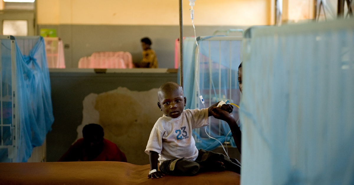 Kagutu Ocam, two and half years old, suffers from malaria. He is being cared by sister Nakawooya Margaret, 14, in the malaria ward at Kiboga Hospital, Kiboga District, Uganda.</p>