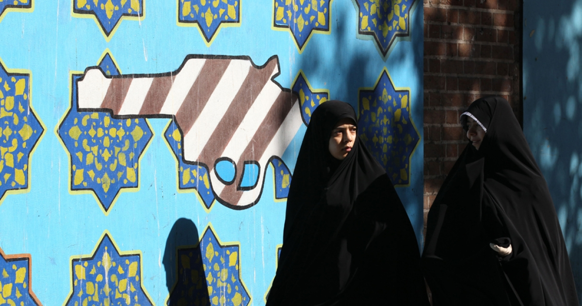 Iranian women walk past a mural of a revolver bearing the colours of the US national flag on the wall of the former US embassy in Tehran on November 2, 2012, during a rally to mark the 33rd anniversary of seizure of the US embassy which saw Islamist students hold 52 diplomats hostage for 444 days.</p>
