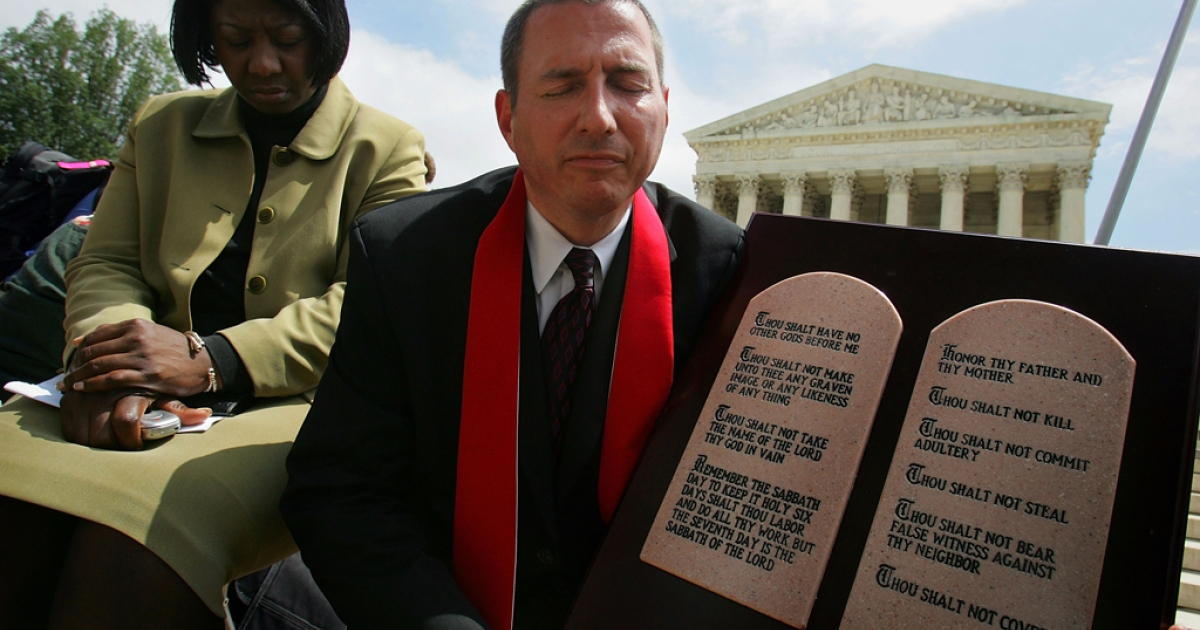 Rev. Rob Schenck and Grace Nwachukwu pray together with a display of the Ten Commandments in front of the Supreme Court in Washington, DC.</p>