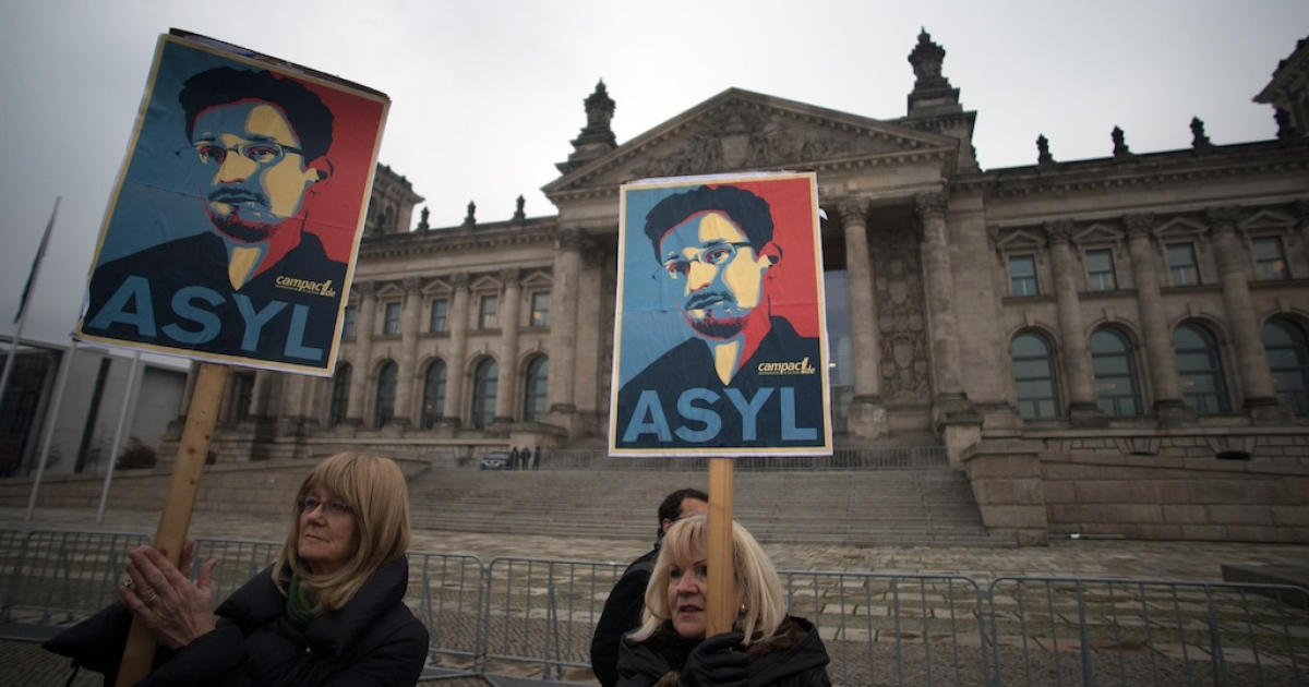 Protesters hold up pictures of US whistleblower Edward Snowden in front of the Reichstag building housing the Bundestag (lower house of parliament) in Berlin on November 18, 2013.</p>