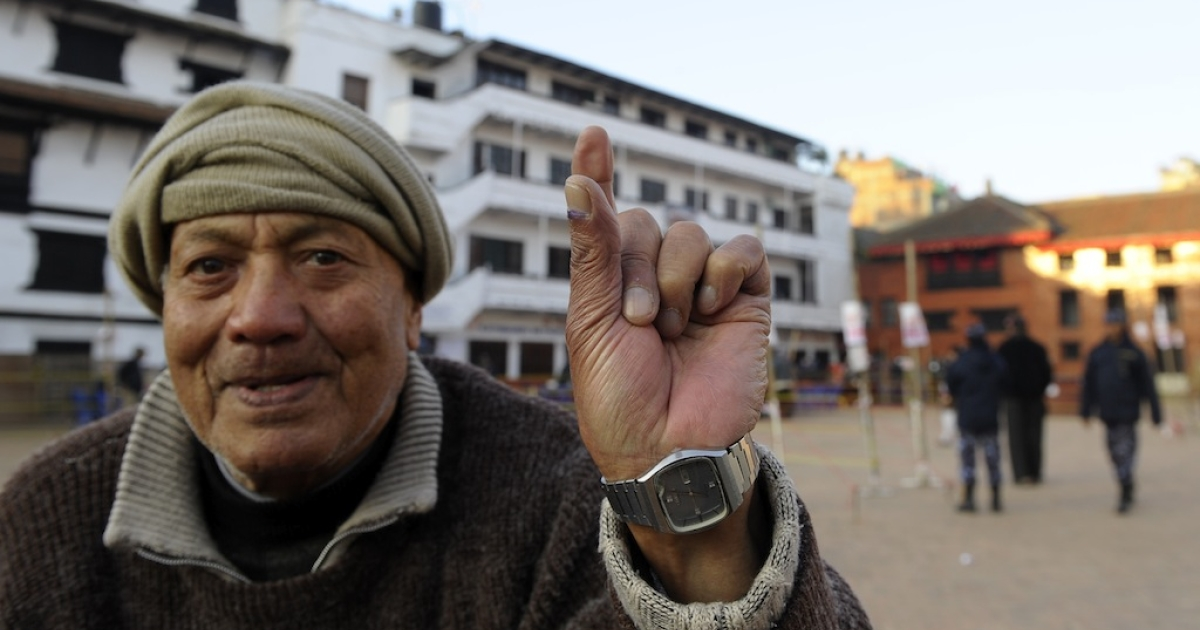 A Nepalese man shows his finger after election official marked it with indelible ink at a polling station in Kathmandu on Novemeber 19, 2013.</p>