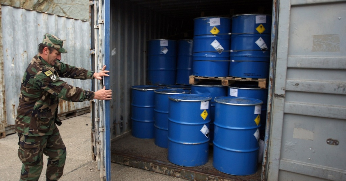 An Albanian soldier closes the door of a container housing 100 tonnes of newly-repackaged hazardous chemical waste at the military base of Qafe Molle near the Albanian capital Tirana on November 20, 2013.</p>