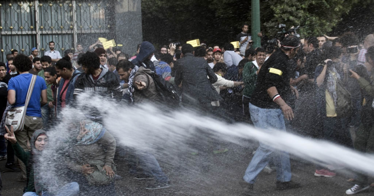 Egyptian policemen use a water cannon to disperse protesters during a demonstration organized by the group