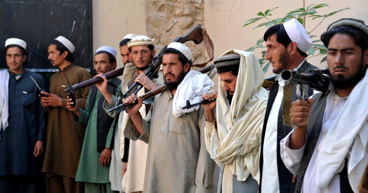 Former Taliban fighters carry their weapons prior to handing them over as they join a government peace and reconciliation process at a ceremony in Jalalabad, capital of Nangarhar province on October 27, 2013.</p>