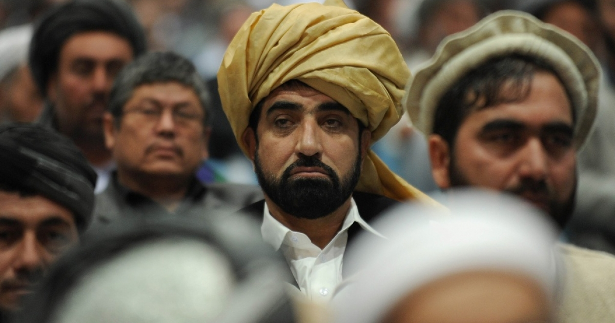 Delegates listen to Afghan President Hamid Karzai deliver a speech during a four-day long loya jirga, a meeting of over 2,000 Afghan tribal elders and leaders in Kabul in November 2011.</p>