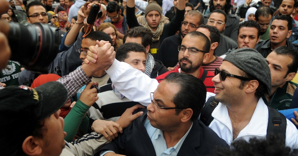 Ahmed Maher (R), co-founder of the 6 April youth movement that spearheaded Mubarak's ousting, is greeted by supporters as he hands himself in to prosecutors on Nov. 30, 2013 in Cairo.</p>