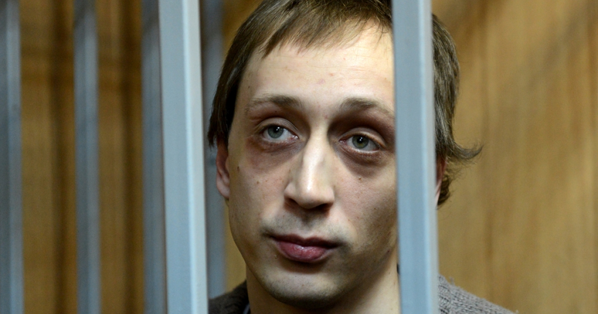 Pavel Dmitrichenko, a former dancer at Russias Bolshoi Theatre, looks on as he stands inside the defendant's cage during a court hearing in Moscow, on October 22, 2013.</p>
