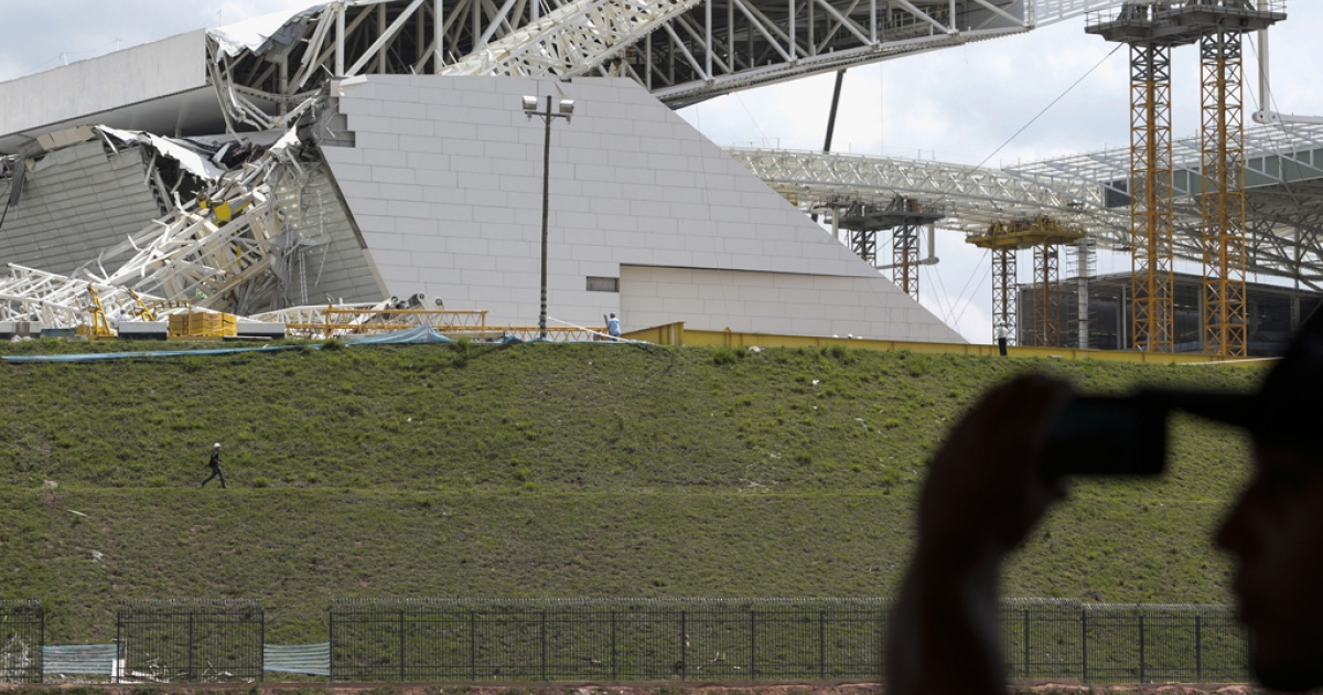 A man takes snapshots of damages at the Arena de Sao Paulo -- Itaquerao do Corinthians -- after a crane fell on Nov. 27, 2013 in Brazil. Two people died and another was injured following the accident on the stadium that will host the opening match of Brazil 2014 FIFA World Cup.</p>