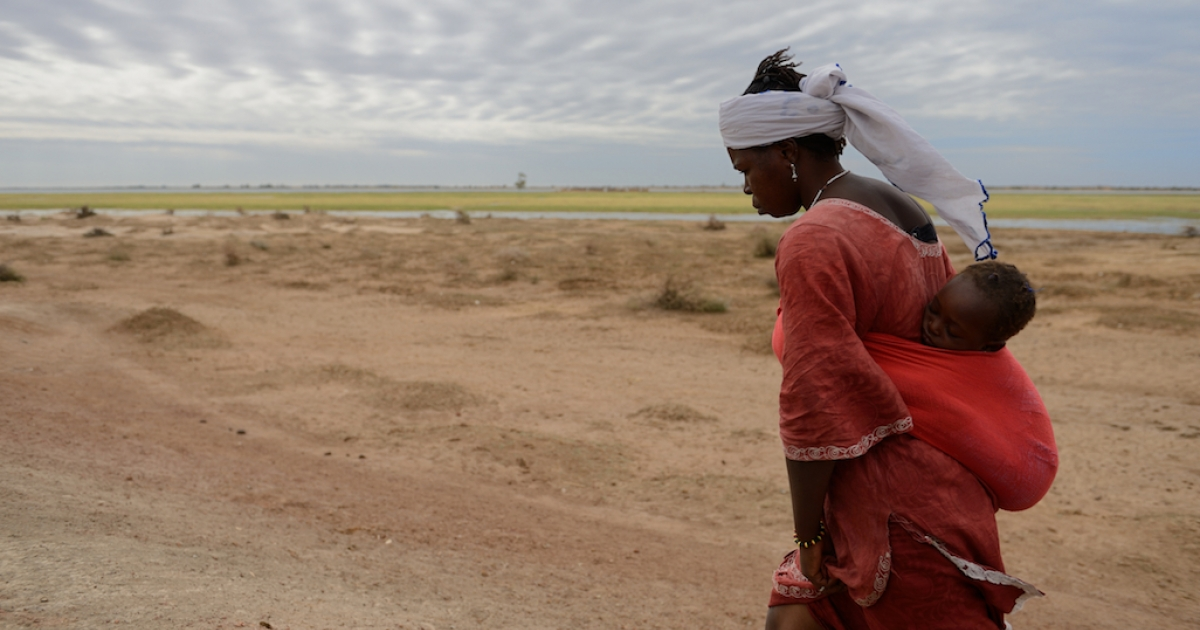 A woman carries her baby in Niafounke, Mali. Climate change is further destabilizing large parts of the Sahel.</p>