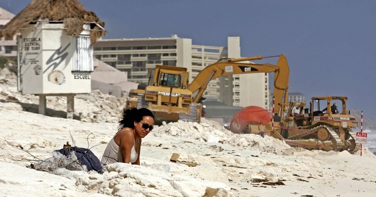 A tourist sunbathes in Cancun in 2006, after Hurricane Wilma devastated the beach. The resort's famous beaches only exist because of multimillion dollar projects to replenish the sand.</p>