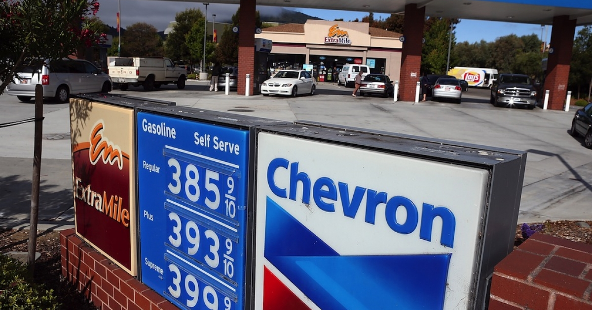 Customers fill up their cars at a Chevron gas station on July 27, 2012 in Greenbrae, California.</p>