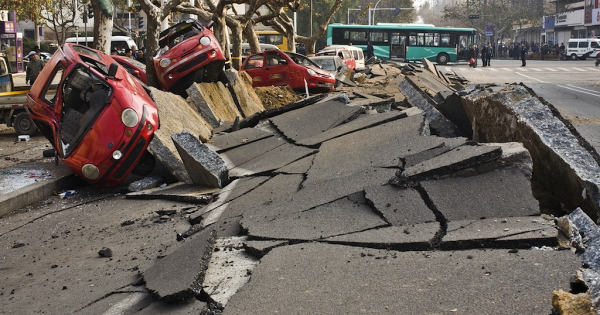 Damaged vehicles lie by a street after an oil pipeline exploded, ripping roads apart, turning cars over and sending thick black smoke billowing over the city of Qingdao, east China's Shandong province on November 22, 2013, killing 35 people, authorities said.</p>