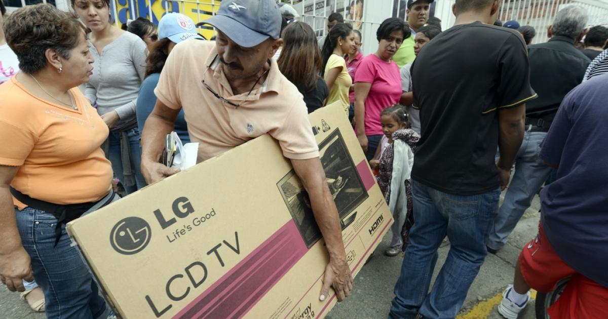 Shoppers loaded with purchases leave a Daka store in Caracas on Nov. 9, 2013. Venezuelan President Nicolas Maduro on Friday ordered the