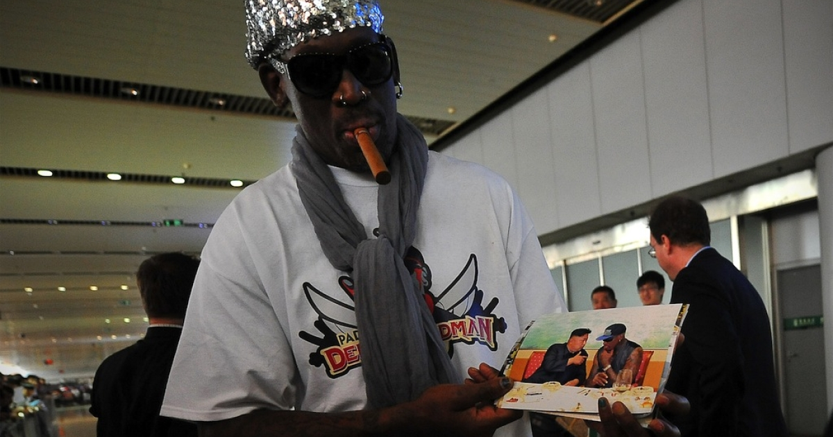 Former US basketball player Dennis Rodman shows pictures of him reportedly with North Korean leader Kim Jong-Un as he arrives at Beijing International Airport on September 7, 2013.</p>