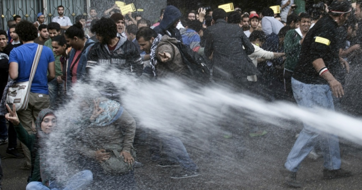 Egyptian police use a water canon to disperse protesters during a demonstration organized by human rights group 'No Military Trials for Civilians' in front of the Shura Council in downtown Cairo on Nov. 26, 2013. A new law passed by Egypt's interim president Adly Mansour requires protesters to obtain permission to demonstrate three days in advance, and allows security forces to issue verbal warnings to protesters, then to use water cannons, tear gas and, finally, birdshot to disperse those who don't comply.</p>