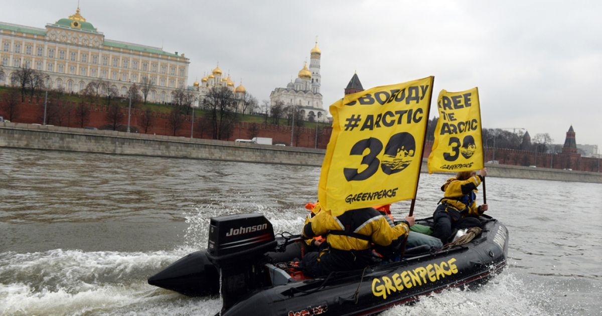 Greenpeace activists hold flags reading