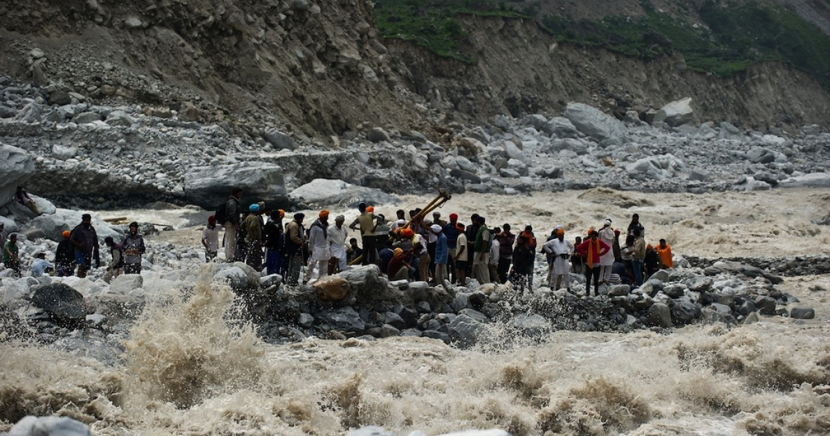 Stranded Indian pilgrims wait to be rescued on the side of a river at Govind Ghat on June 23, 2013.  More than 6,000 died in landslides and flash floods that left pilgrims and tourists stranded without food or water for days.  Scientists expect such deadly glacial deluges to grow more frequent.</p>