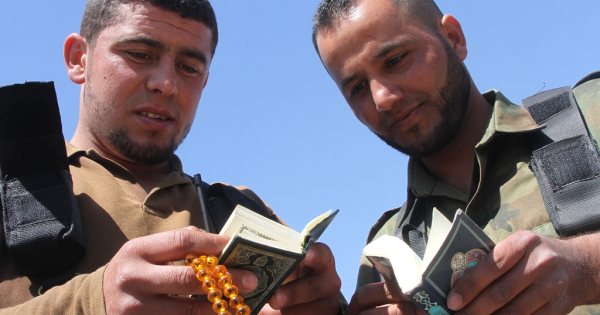 Two FSA fighters read the Koran while on duty in Jabal al Zawia last year.</p>