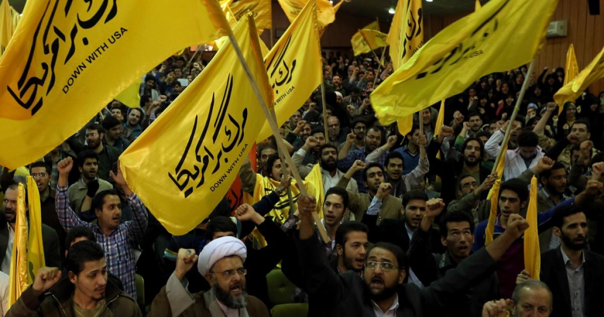 Iranians from the Islamic hardline Basiji militia hold flags reading