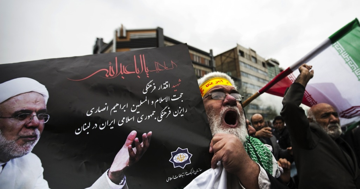 An Iranian man holds a picture of Iran's late cultural advisor to Lebanon, Ebrahim Ansari, as he shouts anti-Israeli slogans during his funeral in Tehran on Nov. 22, 2013.</p>