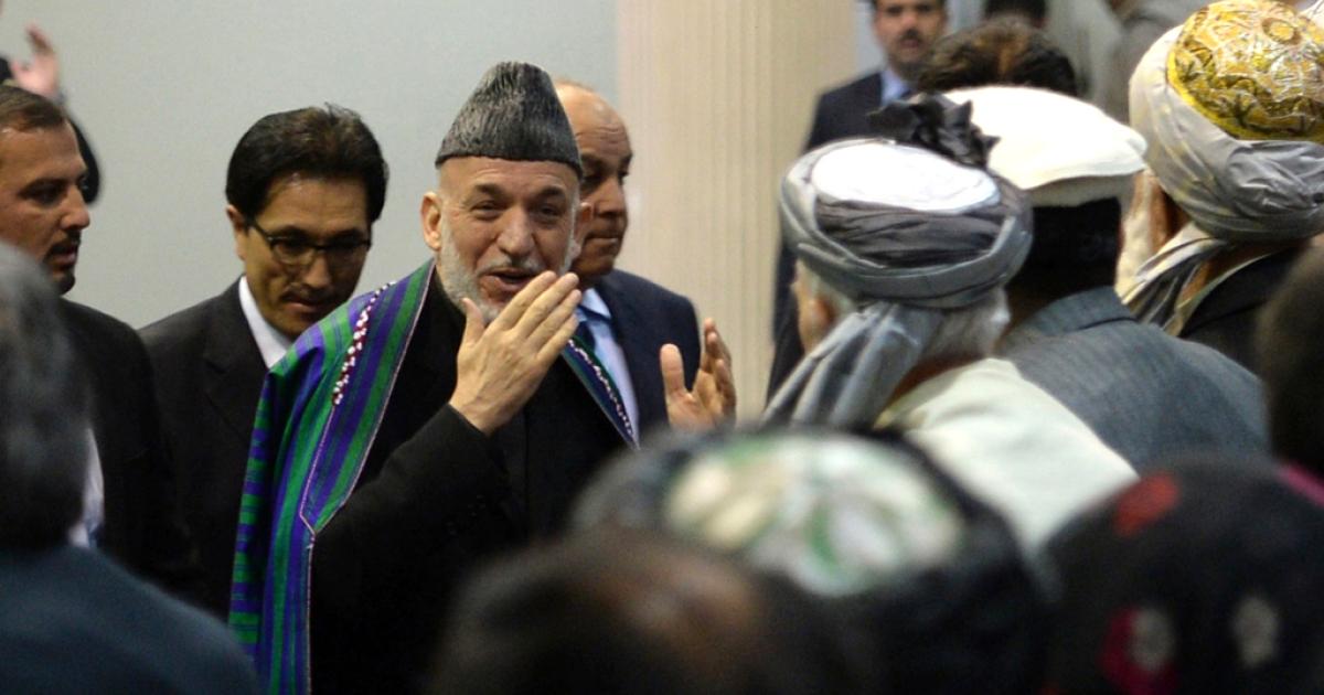 Afghan President Hamid Karzai (C) arrives to address the Afghan Loya Jirga, a meeting of around 2,500 Afghan tribal elders and leaders, on November 21, 2013 in Kabul.</p>