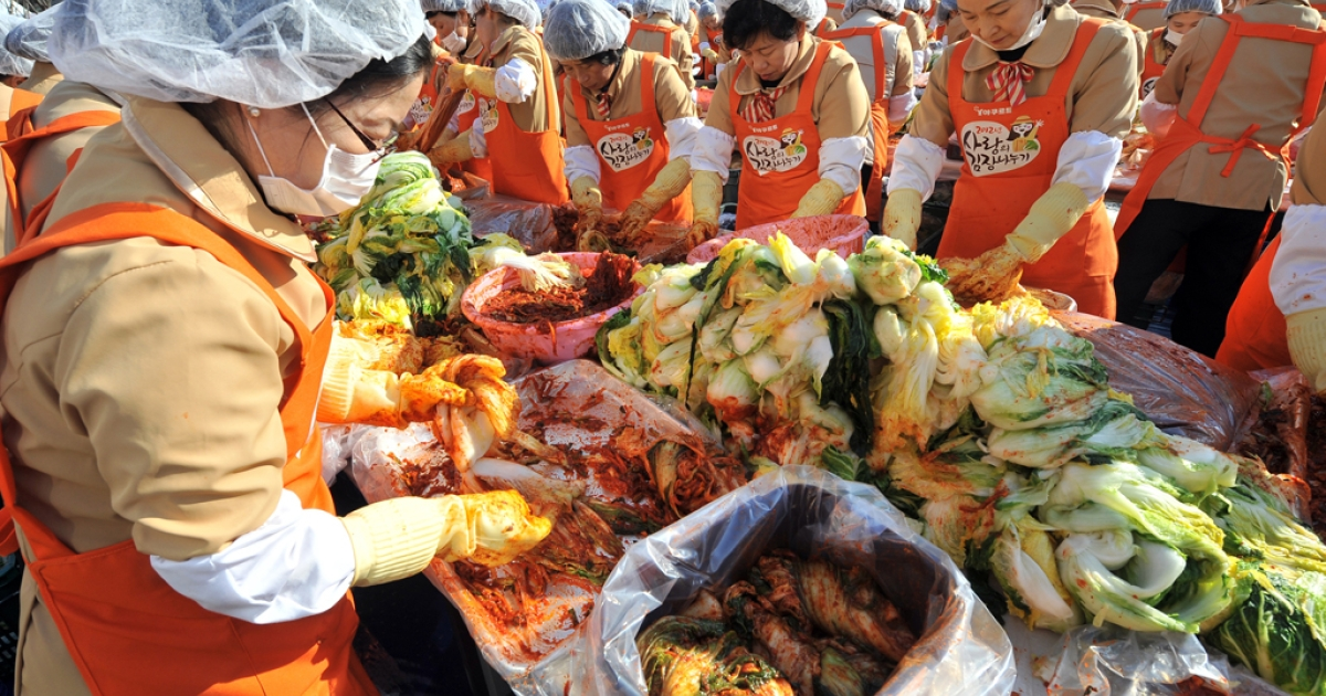 South Korean volunteers make 140 tons of kimchi, a traditional Korean dish of spicy fermented cabbage and radish, in a park outside the metropolitan government building in Seoul on November 15, 2012.</p>