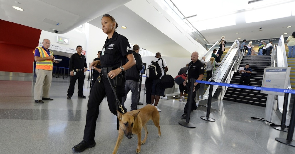 LOS ANGELES, CA - NOVEMBER 2: A Los Angeles Police Department officer and her canine leave after making a sweep of the re-opened Terminal 3 a day after a shooting at Los Angeles International Airport November 2, 2013 in Los Angeles, California. The airport is almost back to normal operations a day after a man pulled out an assault rifle and shot his way through security at Terminal 3, killing one Transportation Security Administration worker and wounding several others.</p>