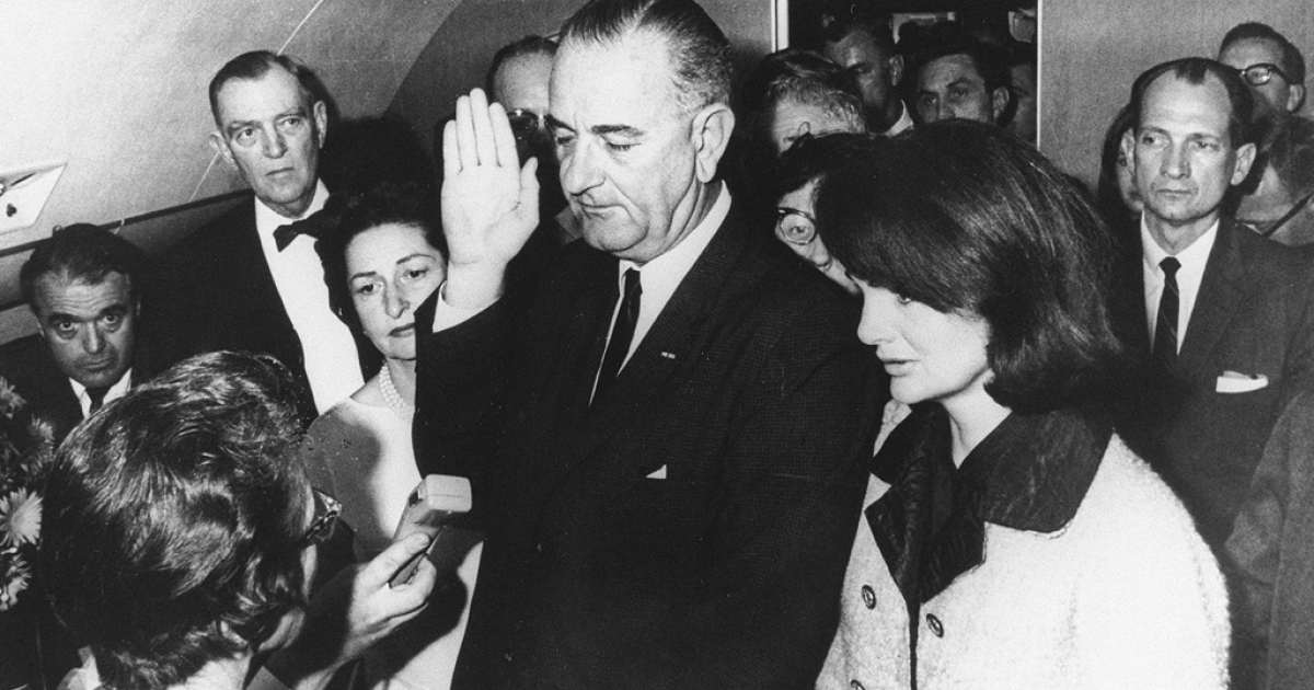 Flanked by Jacqueline Kennedy, right, and his wife Lady Bird Johnson, second left, Lyndon Johnson takes the oath of office of president following the assassination of President John F. Kennedy in Dallas, Nov. 22, 1963.</p>
