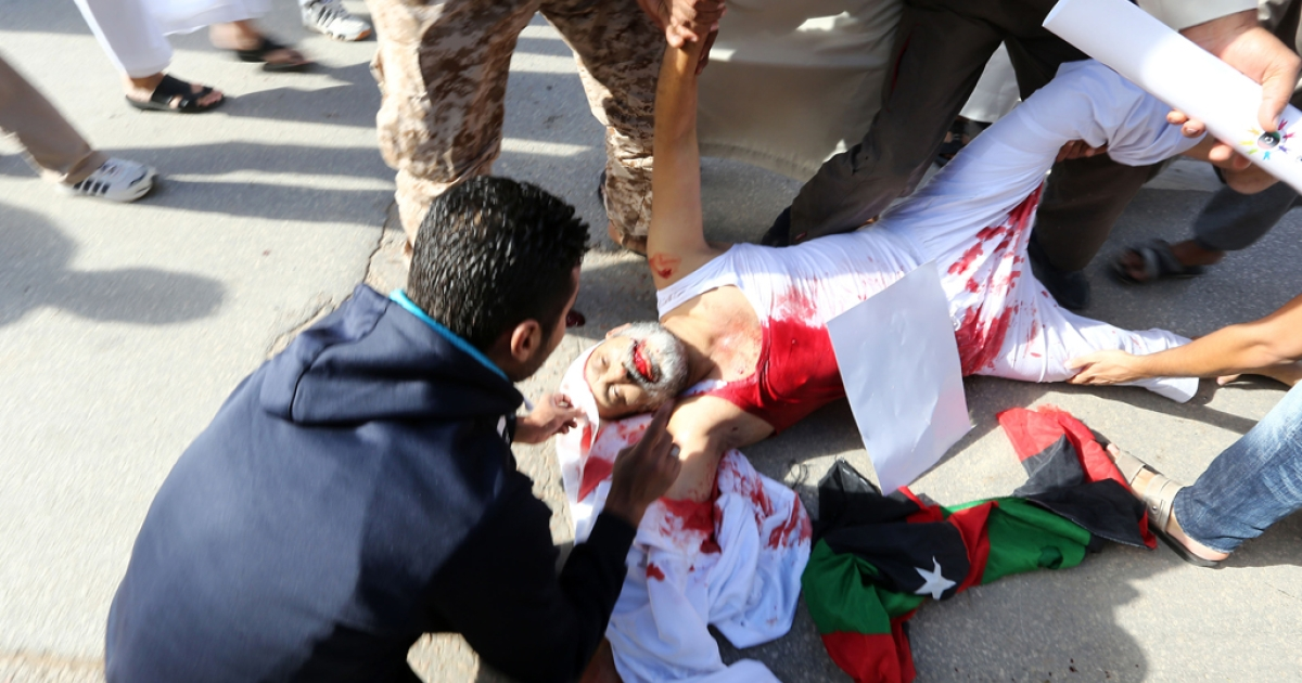 People assist a man who was injured after Libyan militiamen opened fire on a crowd wanting them to move out of their headquarters on November 15, 2013 in southern Tripoli.</p>