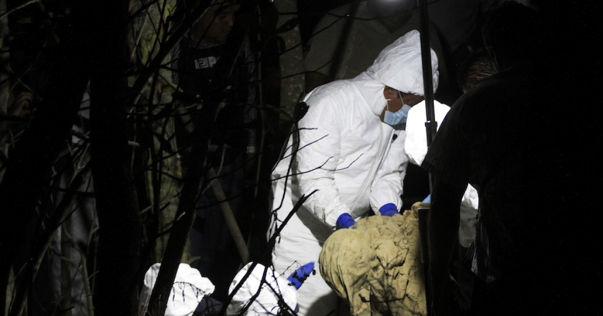 Forensic investigators recover one of three bodies found in a mass grave near El Arenal in the western state of Jalisco on April 17, 2013.</p>