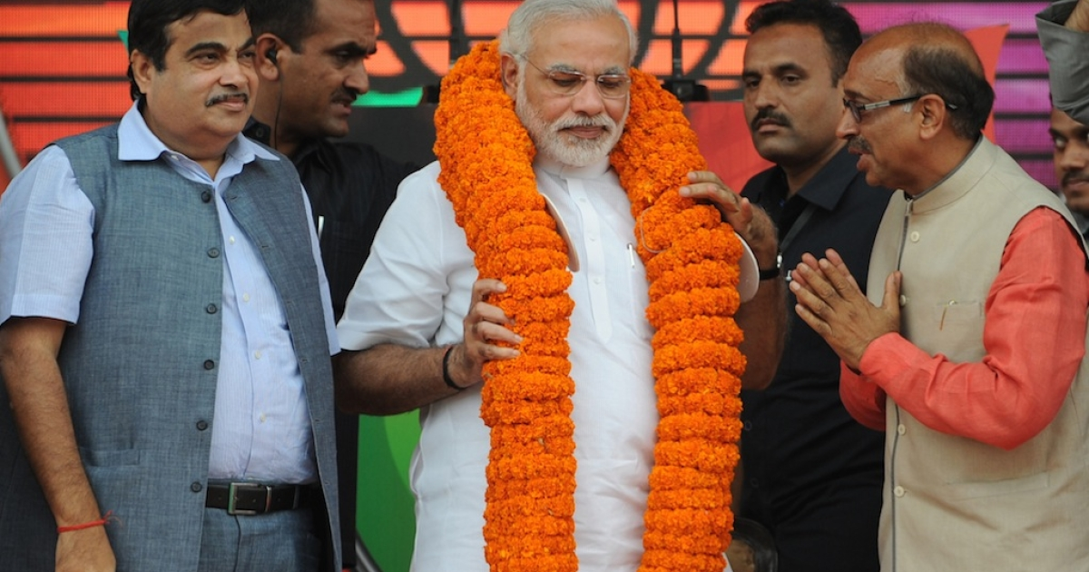 Gujarat state Chief Minister and the Bharatiya Janata Party's (BJP) prime ministerial candidate, Narendra Modi (C) wears a garland as he greets supporters during an election rally in New Delhi on September 29, 2013.  Goldman Sachs recently reported that he's viewed favorably by investors. Not everyone agrees.</p>