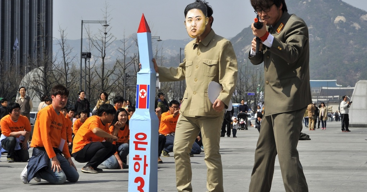 A South Korean activist (C) wearing a mask of North Korean leader Kim Jong-Un holds a mock missile during a rally denouncing North Korea's rocket launch and the three-generational dictatorship, in Seoul on April 15, 2012. Some of the