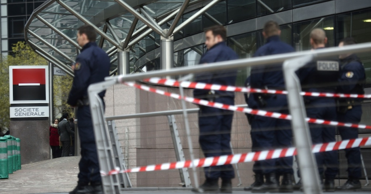 Police stand outside the entrance of the headquarters of the Société Générale bank in the La Défense business district, on the western outskirts of Paris on November 18, 2013, where a number of gun shots were fired and no one was injured. The incident comes several hours after a 27-year-old man was left fighting for his life after being shot by an intruder at the Paris offices of left-wing French daily Libération.</p>