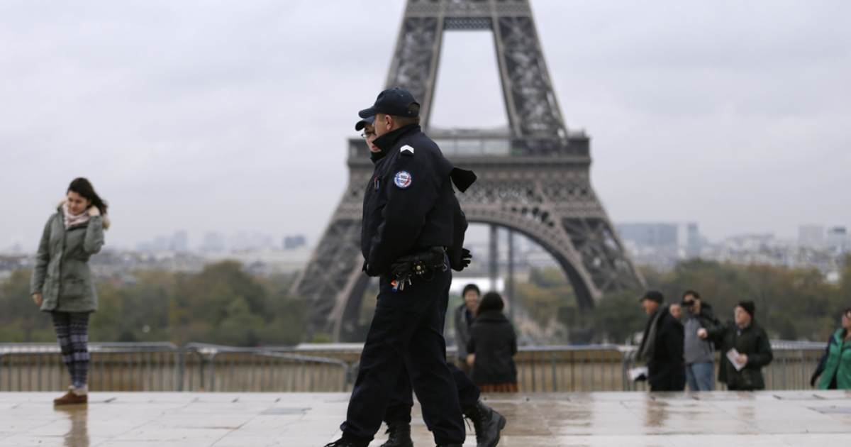 Police officers patrol in front of the Eiffel Tower in Paris on November 19, 2013 as a manhunt is under way in Paris for a lone gunman who shot and critically wounded a newspaper photographer in his office on November 18.</p>