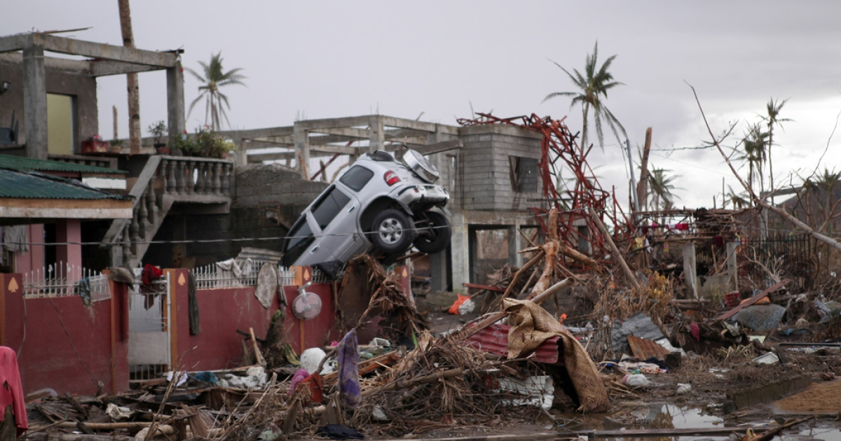 An SUV rests on a wall in the aftermath of typhoon Haiyan on Nov. 17, 2013 in Tanauan, Leyte, Philippines.</p>