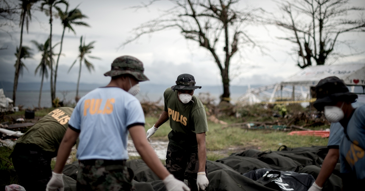 Dead bodies are unloaded at a makeshift morgue in Tacloban, on the eastern island of Leyte on November 12, 2013 after Super Typhoon Haiyan swept over the Philippines.</p>