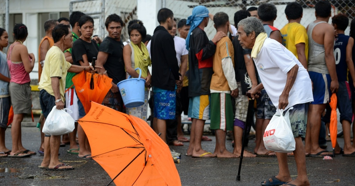 Typhoon victims in Tacloban, a city on the eastern island of Leyte, line up for relief goods in the aftermath of Super Typhoon Haiyan on Nov. 9, 2013.</p>