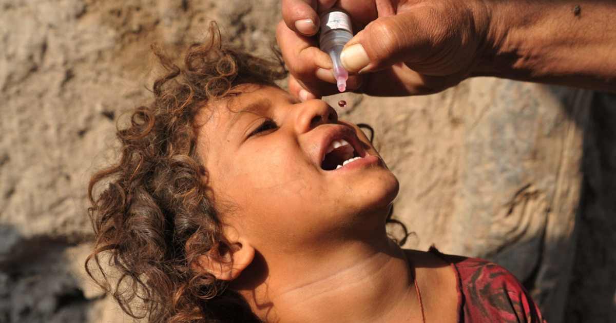 An Afghan health worker administers a polio vaccination to a child on the first day of a vaccination campaign on the outskirts of Jalalabad, Nangarhar province on October 6, 2013.</p>