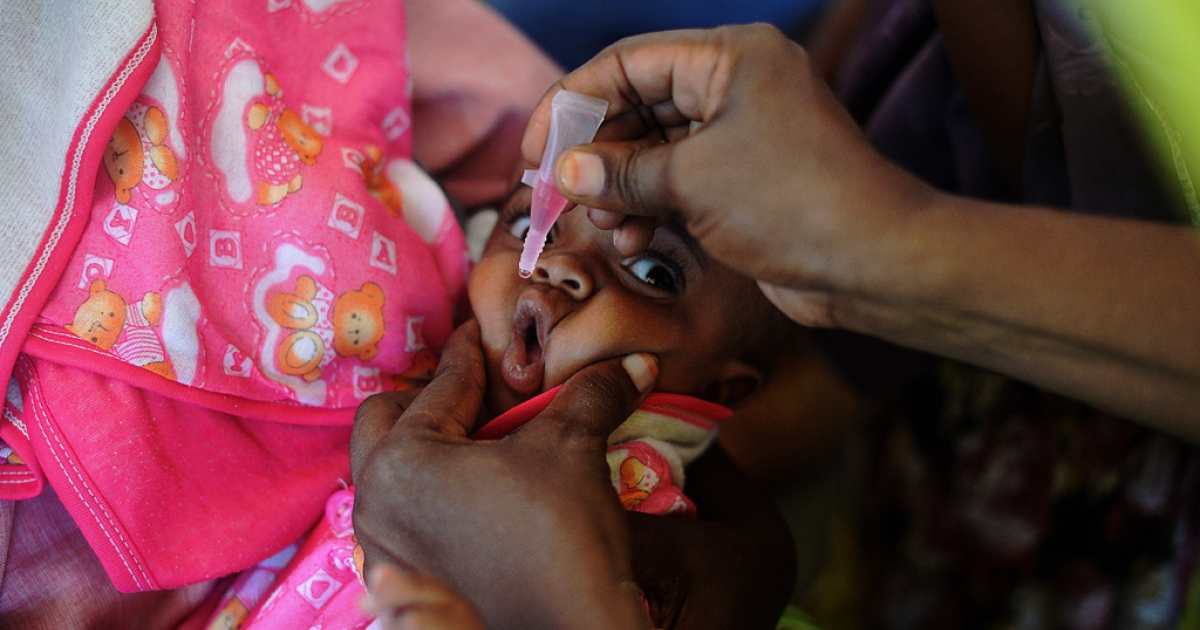 A Somali baby is given a polio vaccination before being given a pentavalent vaccine injection at a medical clinic in Mogadishu on April 24, 2013.</p>