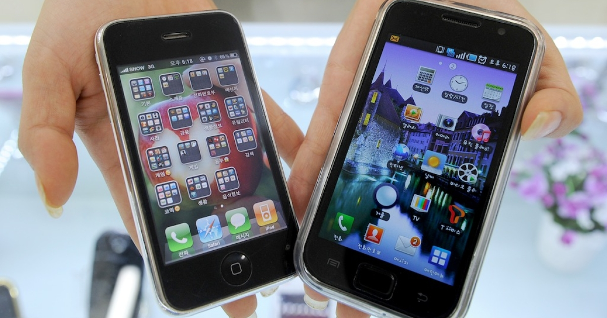 A South Korea shop manager shows Samsung Electronics' Galaxy S mobile phone (R) and Apple's iPhone 3G in July, 2010. Although Samsung has been ordered to pay nearly a billion dollars to Apple for patent infringements, the two companies remain dependent on one another.</p>