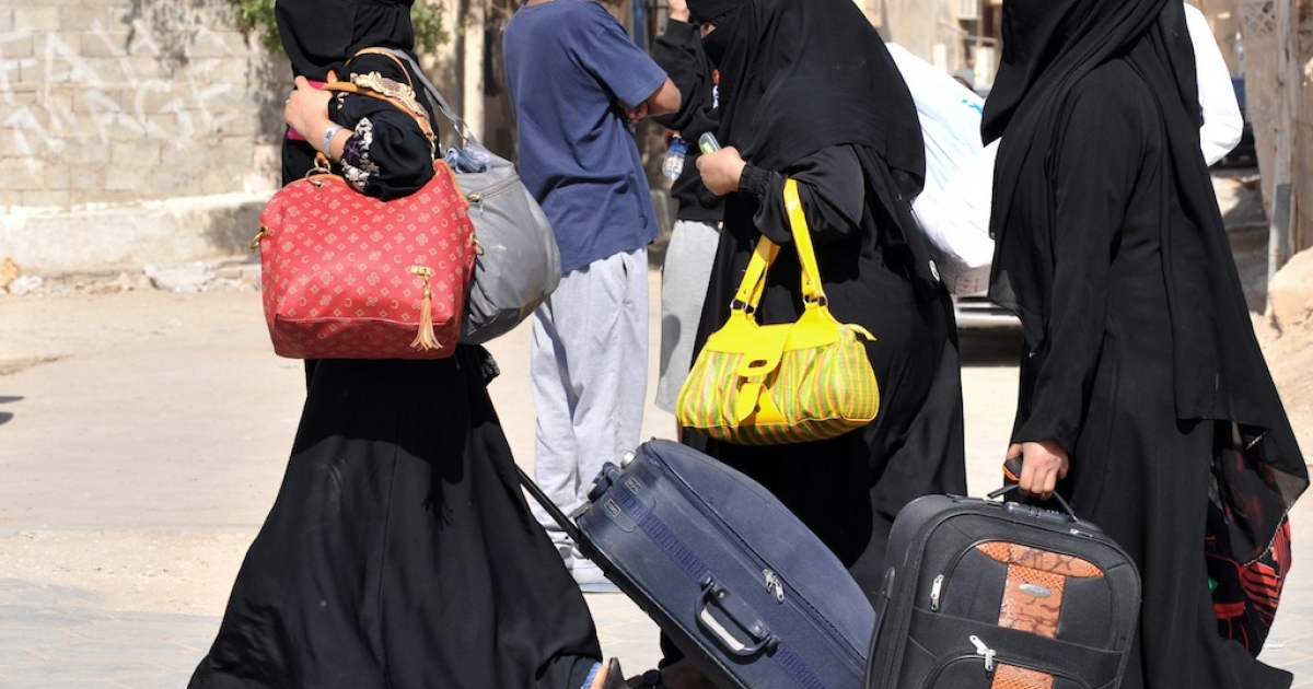 Foreign workers carry their belongings as they leave the Manfuhah neighborhood of Riyadh on Nov. 10, 2013.</p>