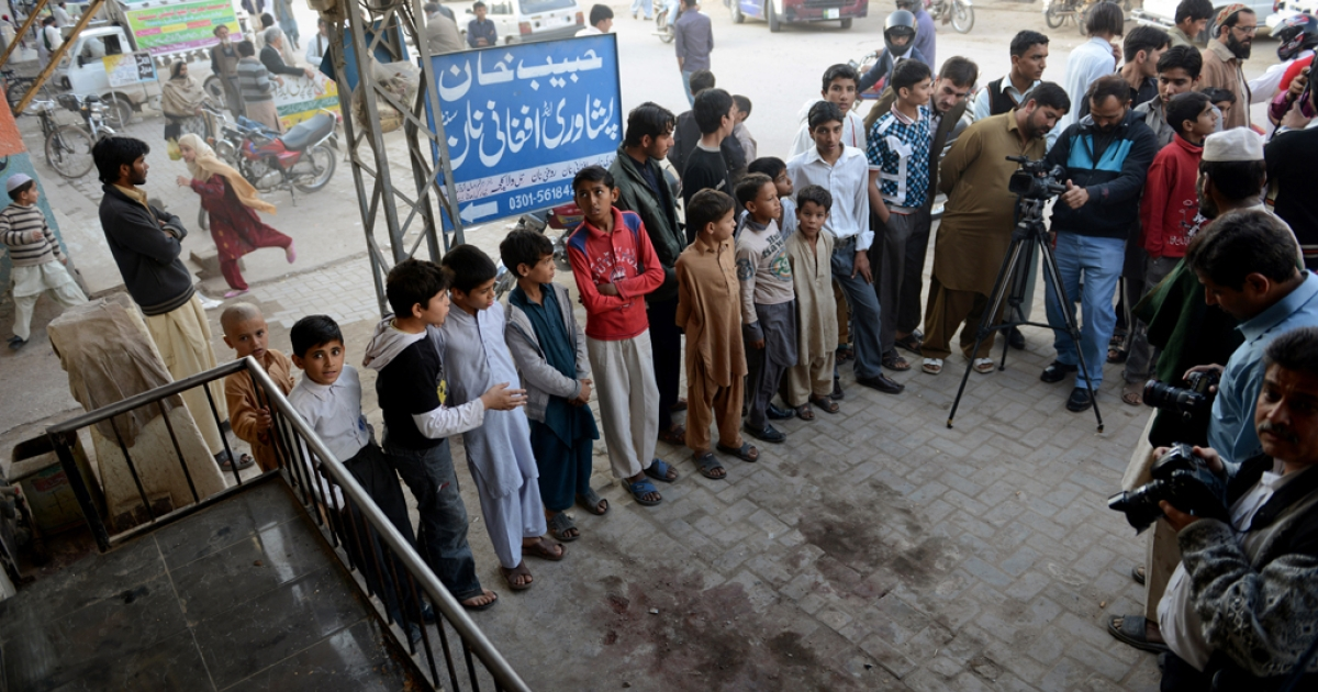 Pakistani youth and onlookers gather at the spot where Nasiruddin Haqqani, a senior leader of the feared militant Haqqani network, was assassinated outside the Afghan bakery in the Bhara Kahu area on the outskirts of Islamabad on November 11, 2013.</p>